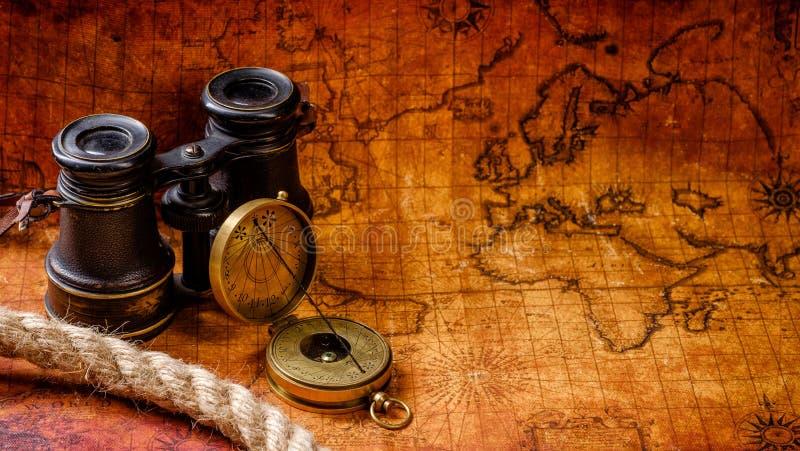 Retro- Kompass und Fernglas der alten Weinlese auf Antikekarte stockbilder