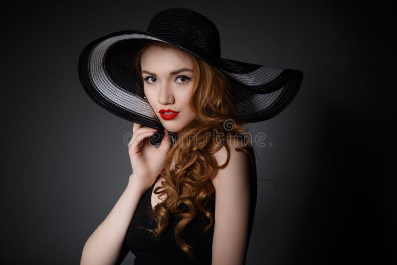 Retro kvinna i stående för hatttappningmode royaltyfria foton