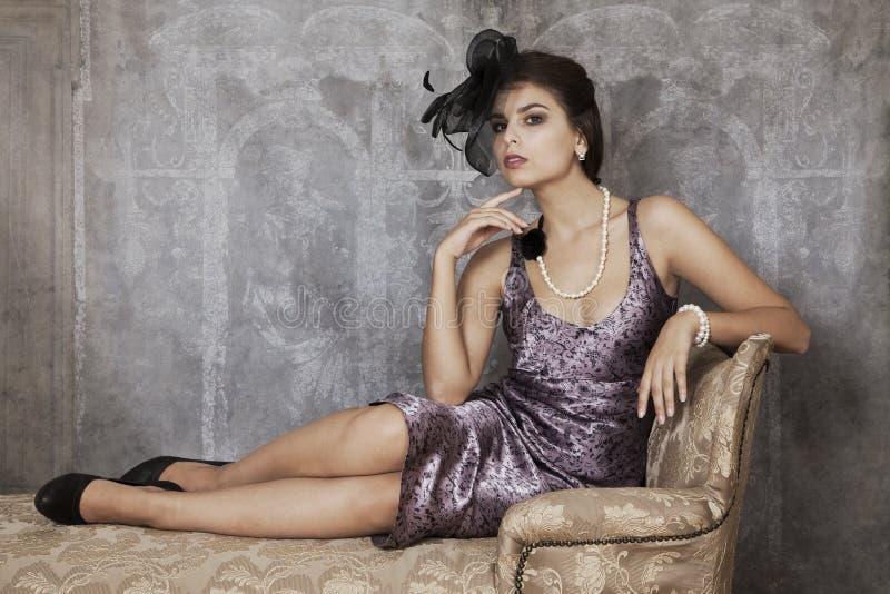 Retro kvinna på den antika soffan royaltyfri bild