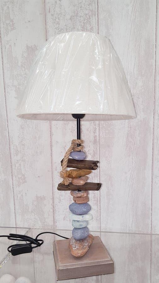 Retro lampa i drivved- och strandkiselstenar royaltyfri foto
