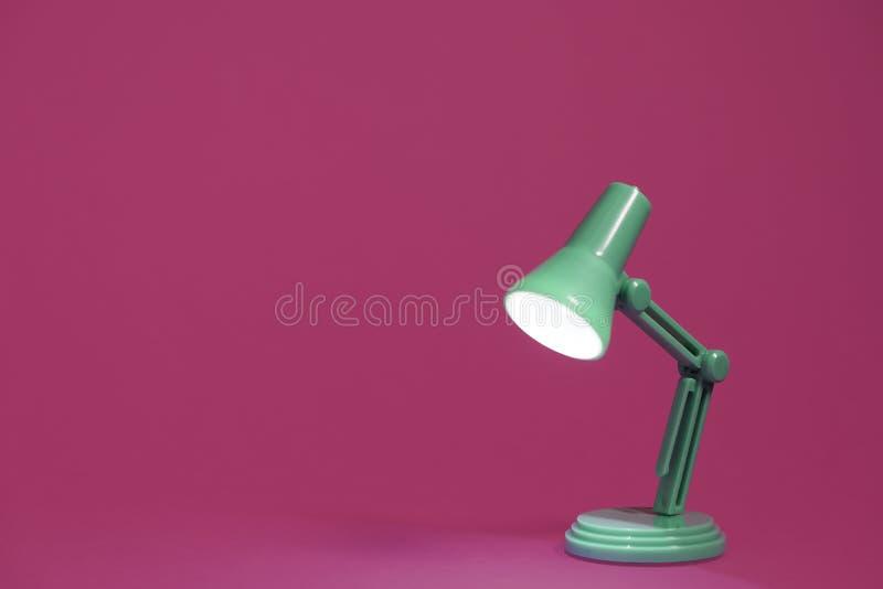 Retro lampada di scrittorio verde sul rosa fotografie stock libere da diritti