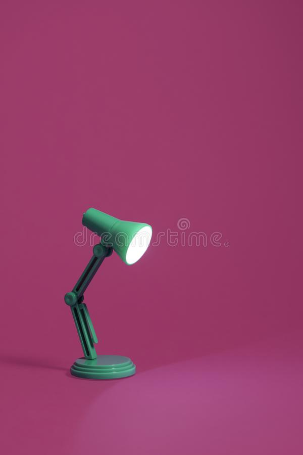 Retro lampada di scrittorio verde sul rosa fotografia stock