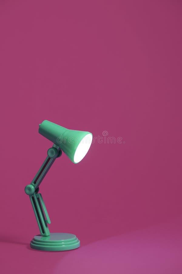 Retro lampada di scrittorio verde sul rosa immagine stock
