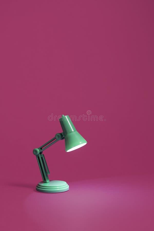 Retro lampada di scrittorio verde sul rosa immagini stock