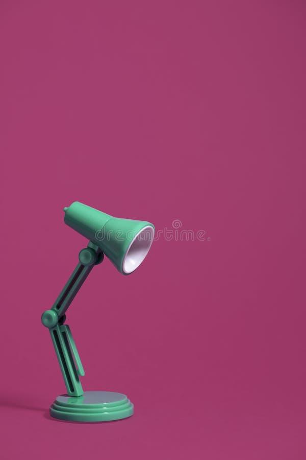 Retro lampada di scrittorio verde sul rosa fotografie stock
