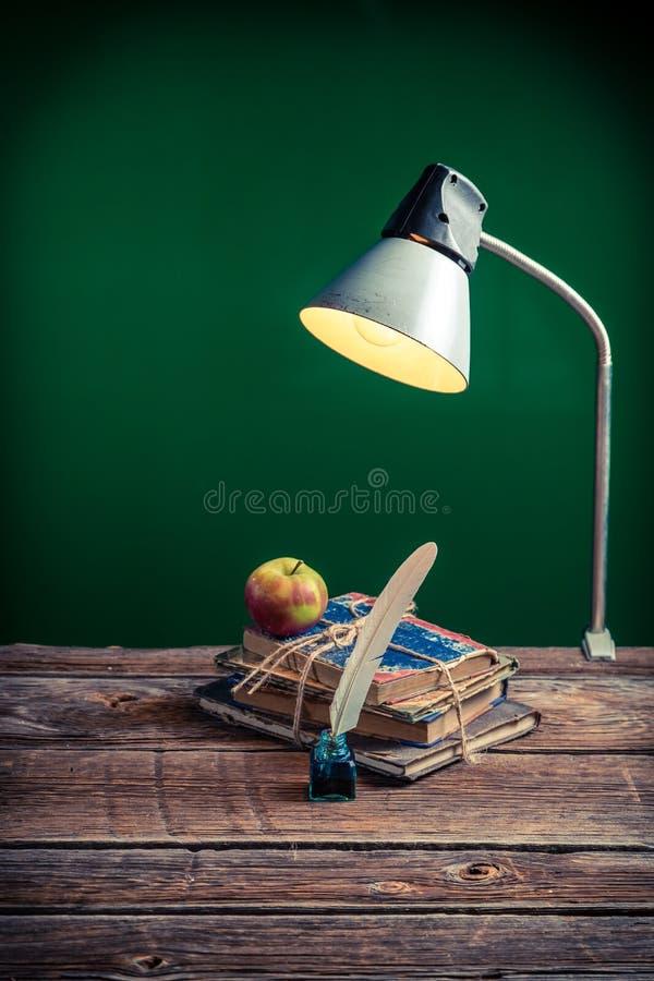 Retro lampada e libri nell'aula fotografia stock