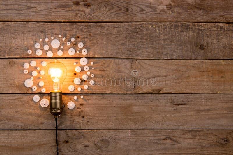 Retro lampadina e gruppo di ingranaggi su fondo di legno - concetto di idea, dell'innovazione, di lavoro di squadra e di direzion illustrazione di stock