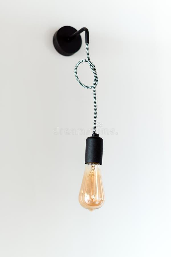 Retro- Lampe Edison Glühbirne auf weißem Wandhintergrund im Dachboden Konzept der Weinleseart lizenzfreie stockfotos