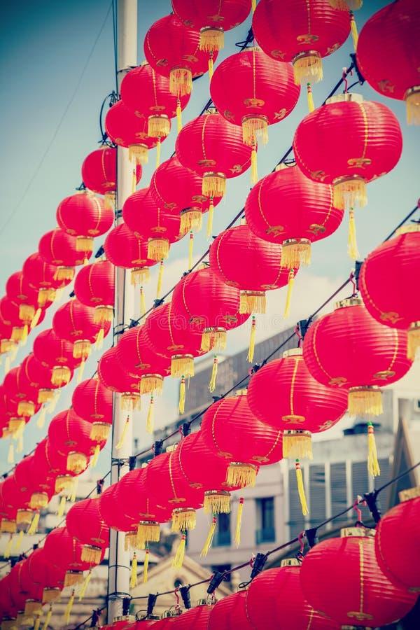 Retro lanterne di carta rosse cinesi filtrate contro cielo blu immagine stock