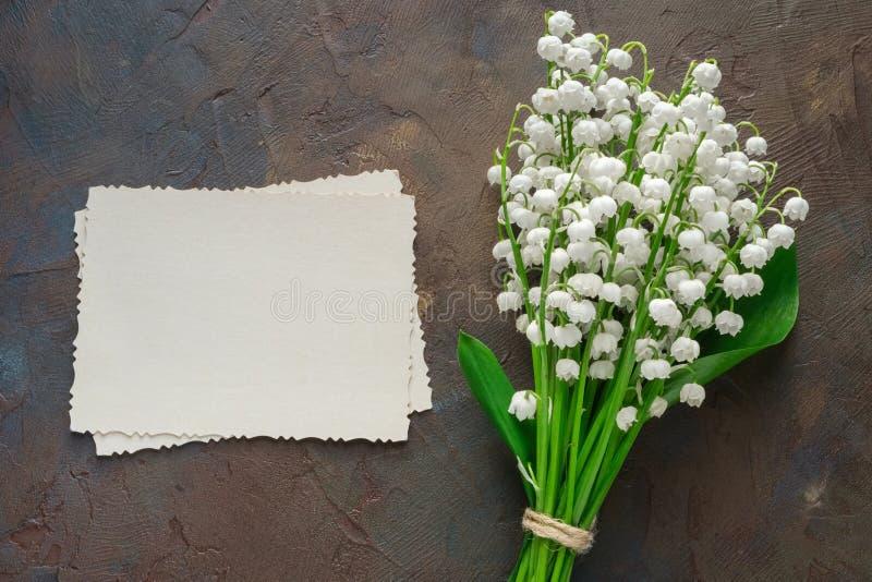 Retro- leerer Fotorahmen f?r das Innere und Maigl?ckchenblumenstrau? auf dunkelbraunem Hintergrund stockbild