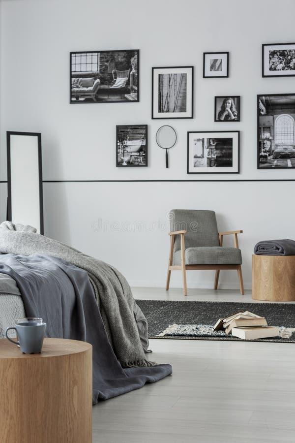 Retro- Lehnsessel im modernen Schlafzimmer Innen mit gemütlicher Bettwäsche auf warmem Bett stockfoto