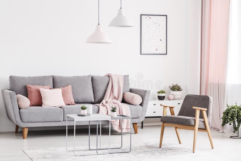 Retro leunstoel, grijze bank met roze binnen hoofdkussens en koffietafels stock fotografie