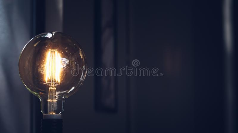 Retro light bulb on dark background with space. Lighting decor macro loft style background royalty free stock images