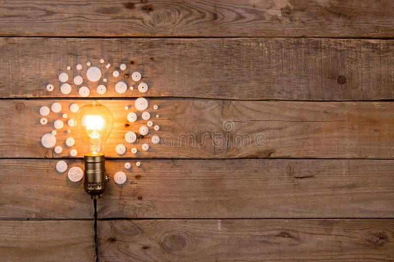 Retro light bulb and group of gears on wooden background - idea, innovation, teamwork and leadership concept. Space for text. Light bulb and group of gears on stock illustration