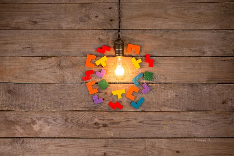 Retro light bulb and group of jigsaws on wooden background - idea, innovation, teamwork and leadership concept. Space for text. Light bulb and group of jigsaws royalty free stock image