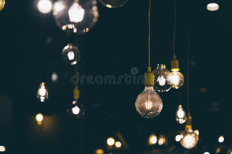 Retro light bulbs hanging in department store, with decorate interior luxury, fixtures combine beautiful modernity Designer, lamps. On the ceiling, beautifully royalty free stock images