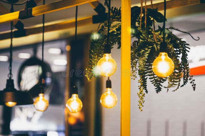 Retro light bulbs hanging in department store, with decorate interior luxury, fixtures combine beautiful modernity Designer, lamps. On the ceiling, beautifully royalty free stock photography