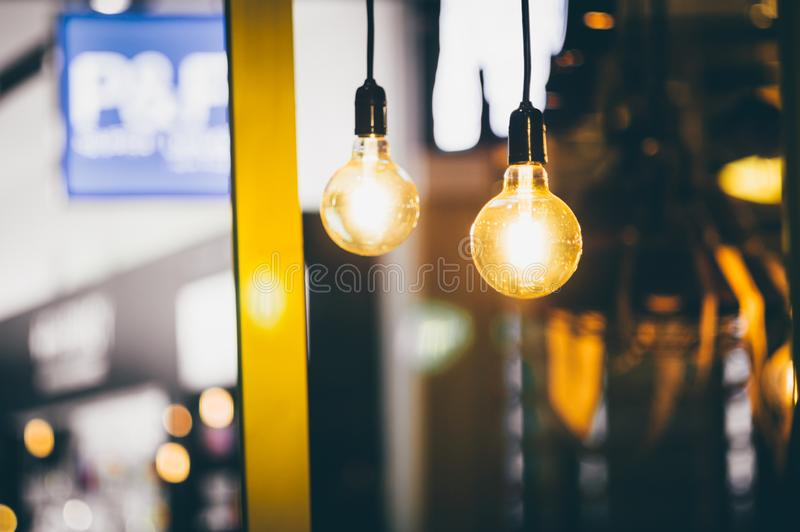 Retro light bulbs hanging in department store, with decorate interior luxury, fixtures combine beautiful modernity Designer, lamps. On the ceiling, beautifully stock image
