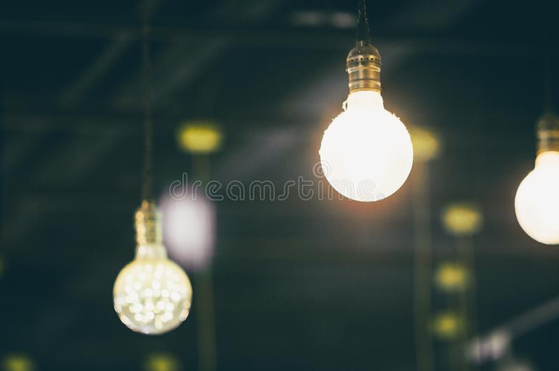 Retro light bulbs hanging in department store, with decorate interior luxury, fixtures combine beautiful modernity Designer, lamps. On the ceiling, beautifully stock photography