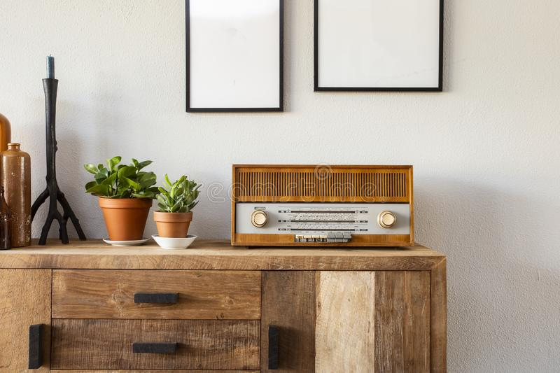 Retro living room design with cabinet and radio along with green plants and blank paintings, white wall royalty free stock image