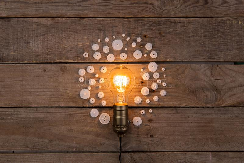 Retro ljus kula och grupp av kugghjul på träbakgrund - idé, arkivbilder