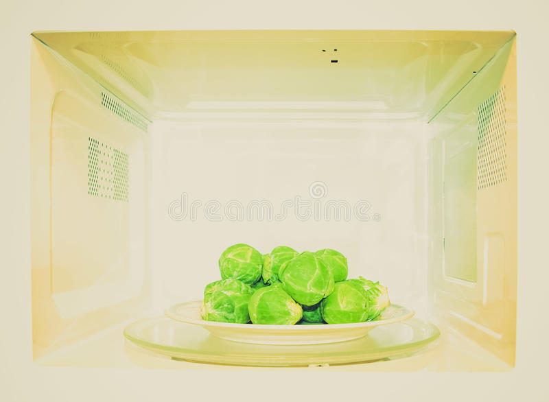 Retro look Microwave oven. Vintage looking Detail of microwave oven with Brussel sprouts stock photography