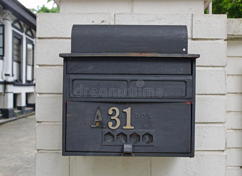 Retro looking rustic outdoor wall attached letter box. Retro looking rustic outdoor wall attached designer letter box with house number 31 stated and little view stock image
