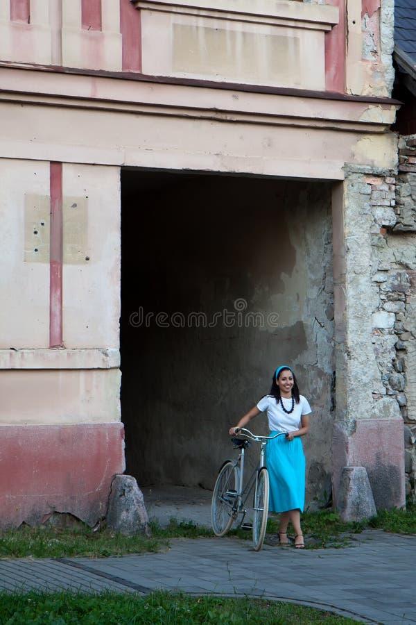 Retro- Mädchen auf altem Fahrrad lizenzfreie stockbilder