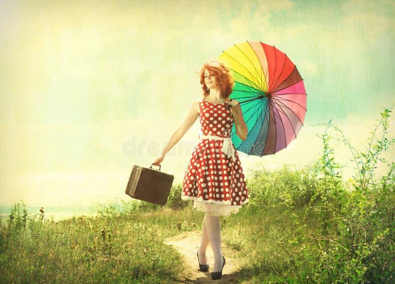 Retro- Mädchen mit einem bunten Regenschirm stockfoto