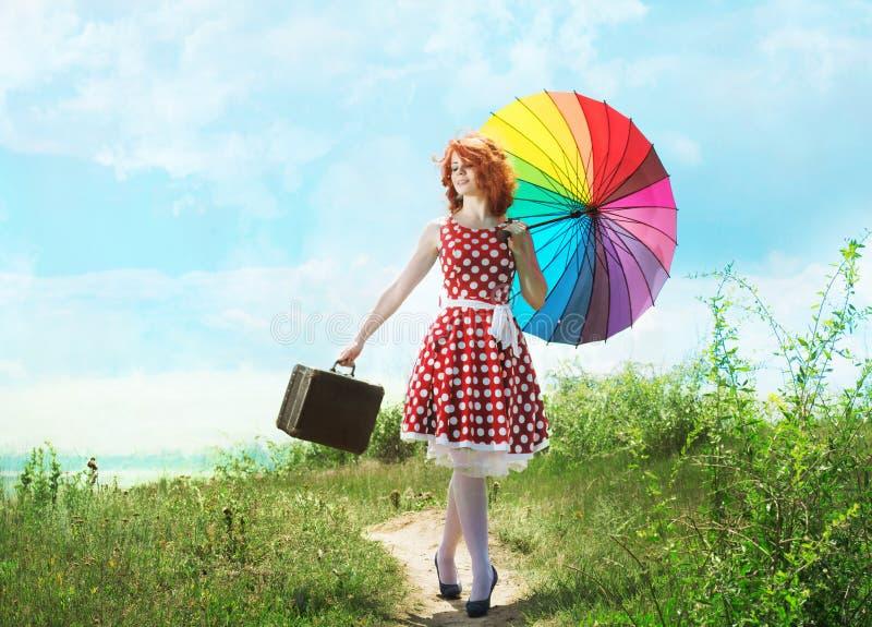 Retro- Mädchen mit einem bunten Regenschirm lizenzfreie stockfotografie