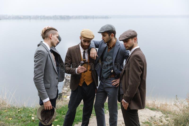 Retro män står mot bakgrunden av en flod arkivbilder