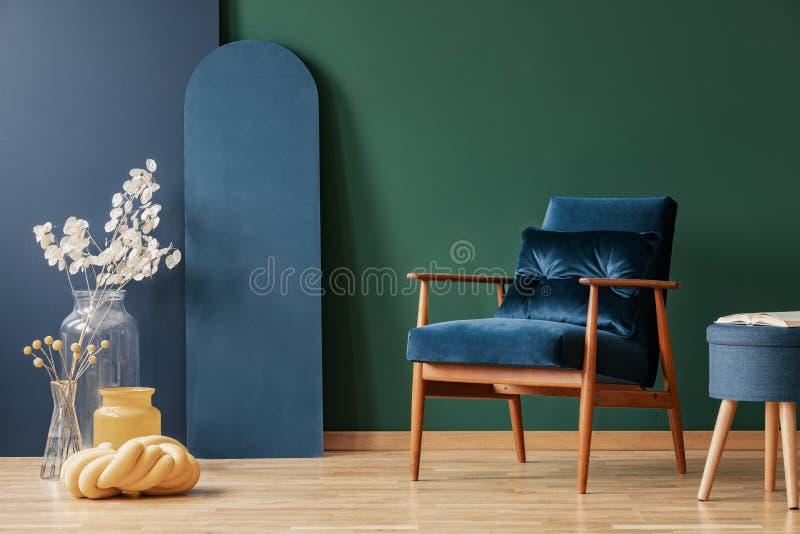 Retro mörkt - blå fåtölj i elegant, vardagsruminre med kopieringsutrymme på den tomma gröna och blåa väggen arkivbilder