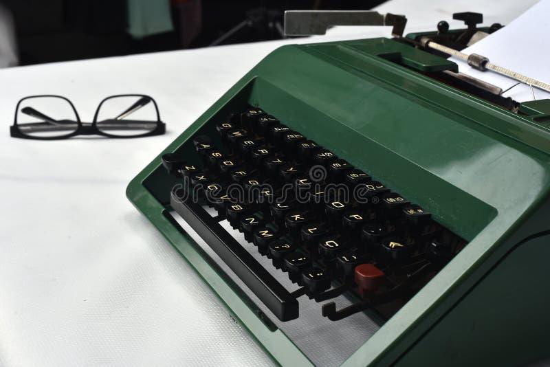 Retro macchina da scrivere antica con carta e vetri accanto su fondo bianco immagini stock libere da diritti