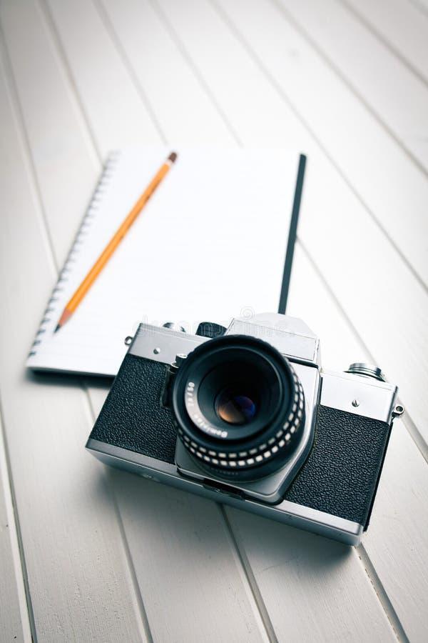 Retro macchina fotografica con il taccuino fotografia stock