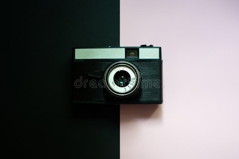 Retro macchina fotografica del film sul nero e su un fondo rosa 5 fotografia stock