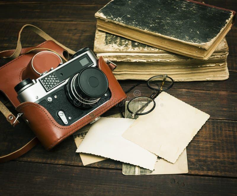 Retro macchina fotografica tranquilla ed alcune vecchie foto sul fondo di legno della tavola fotografia stock libera da diritti