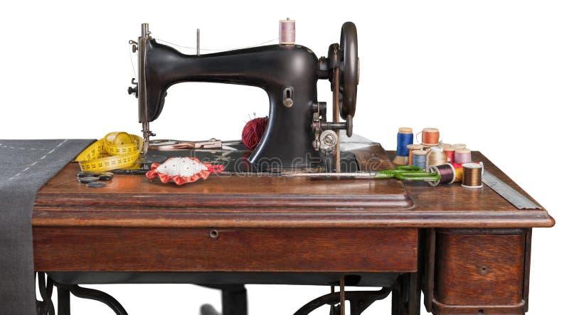Retro macchina per cucire con i rifornimenti isolati sopra fotografia stock