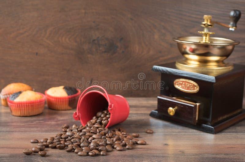 Retro macinacaffè, tazza di caffè del mulino di caffè, bigné del cioccolato, muffin, chicchi di caffè Backg di legno fotografia stock