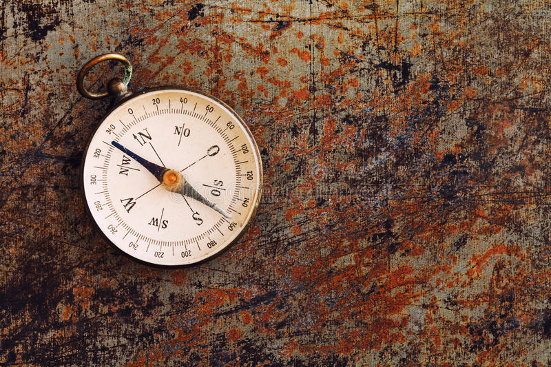 Retro magnetic compass on textured rusty metal background. Geographic exploration navigating instrument for searching stock photos