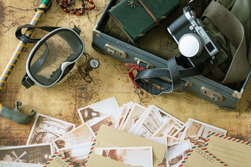 Retro maskering och snorkel med en resväska, en anteckningsbok, en gamla översikt och vykort och en lopputrustning royaltyfria foton