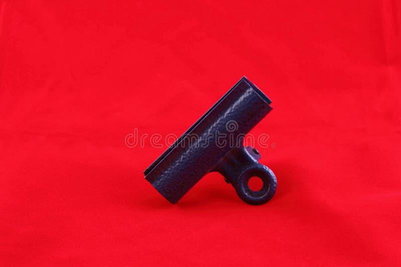 Retro- Metallclip auf rotem Hintergrund stockfotografie