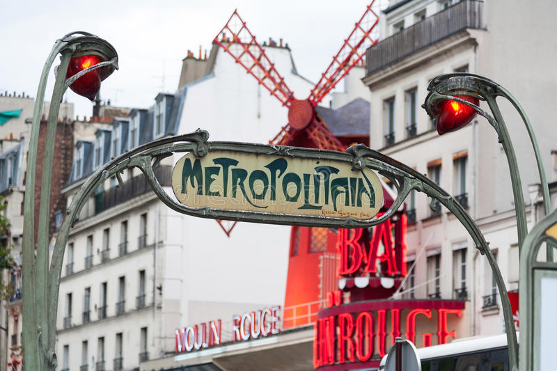 A retro Metro sign in Paris. With the Moulin Rouge behind royalty free stock photo