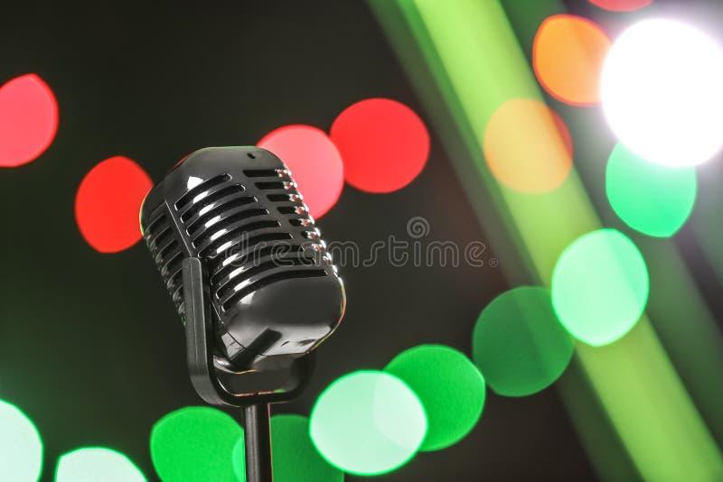 Retro microfono contro le luci festive Strumentazione musicale immagini stock