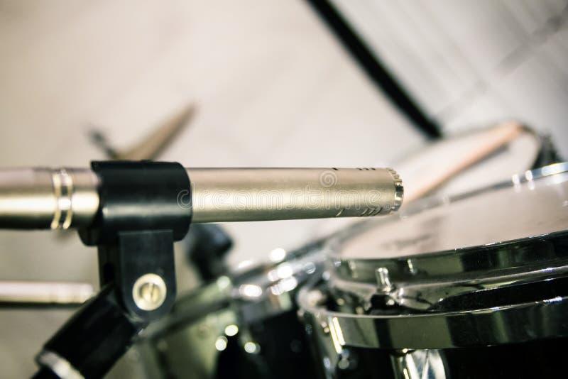 Retro microfono professionale disposto vicino ai tamburi con i bastoni fotografie stock