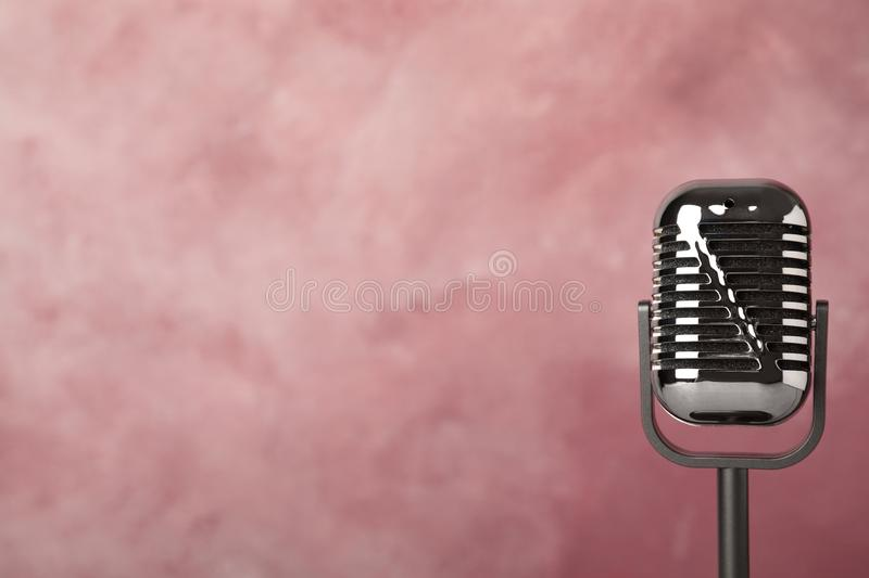 Retro microphone on color background. Space for text royalty free stock image