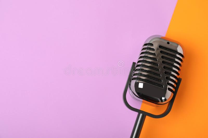 Retro microphone on color background, top view. With space for text royalty free stock image