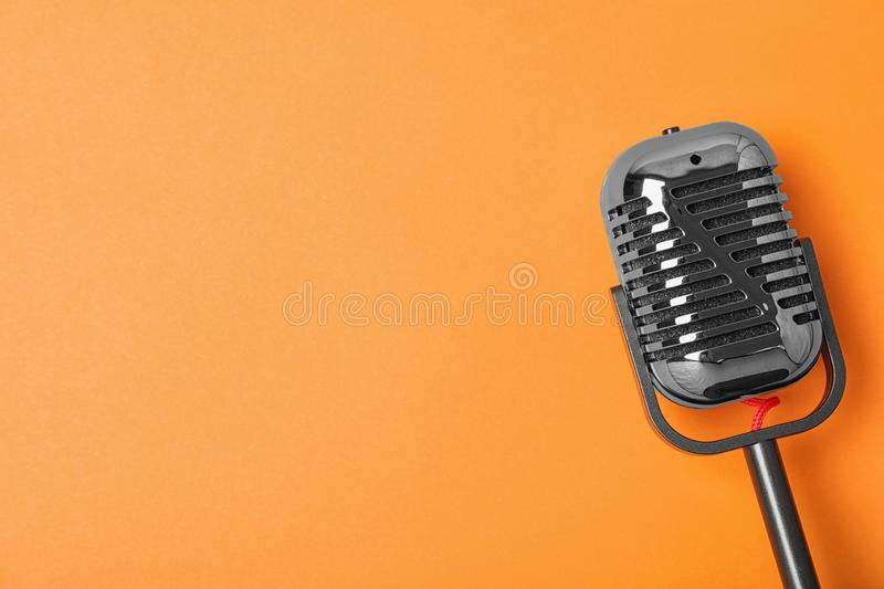 Retro microphone on color background, top view with space for text. Musical equipment stock photo
