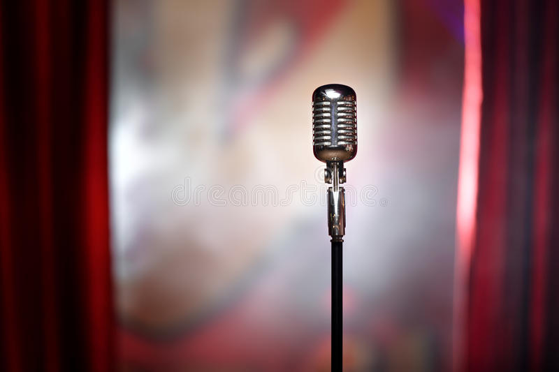 Retro microphone and red curtain. The microphone in front of red curtain on an empty stage after the concert, smoke stock photos