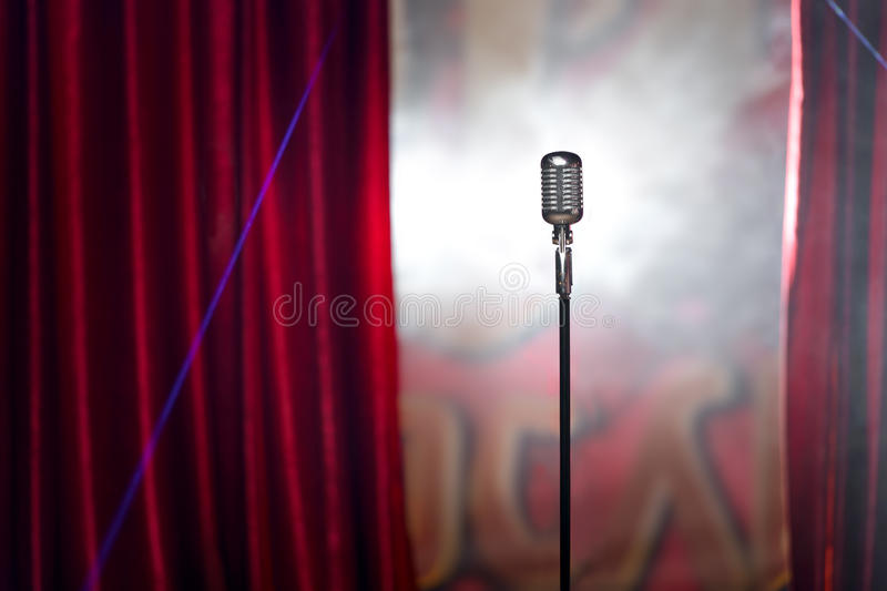 Retro microphone and red curtain. The microphone in front of red curtain on an empty stage after the concert, smoke royalty free stock image