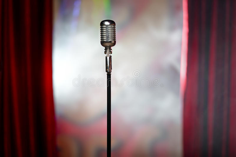 Retro microphone and red curtain. The microphone in front of red curtain on an empty stage after the concert, smoke stock images